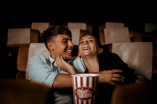Koppel kijken naar film in theater met popcorn glimlach en blij gezicht