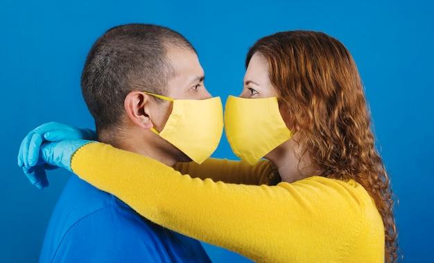 Koppel knuffel en kus met maskers om zichzelf te beschermen tegen coronavirus