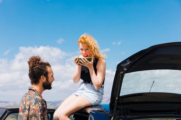 Koppel met auto watermeloen in openlucht eten