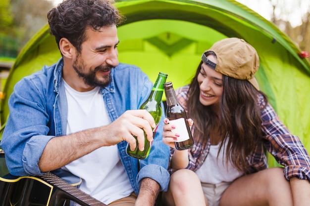 Koppel met bier dichtbij tent