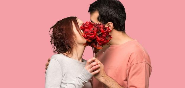 Koppel met bloemen en kussen over geïsoleerde roze achtergrond