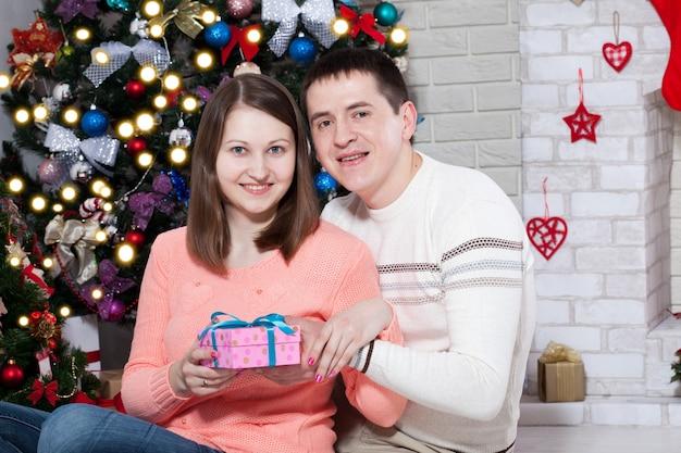 Koppel met cadeau samen genieten op kerstavond thuis