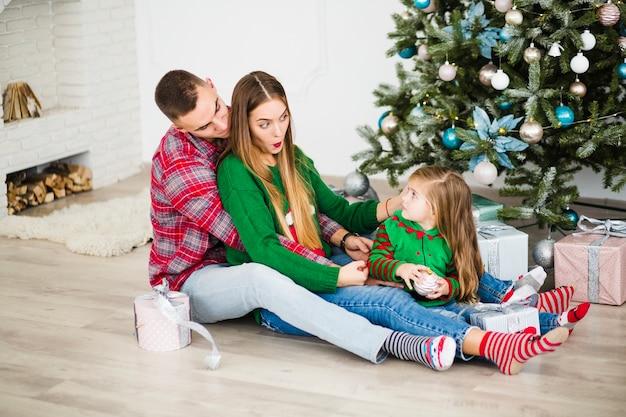 Koppel met dochter naast kerstboom