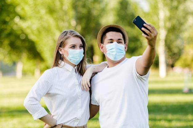 Koppel met een masker een selfie maken met hun mobiele telefoon in het park