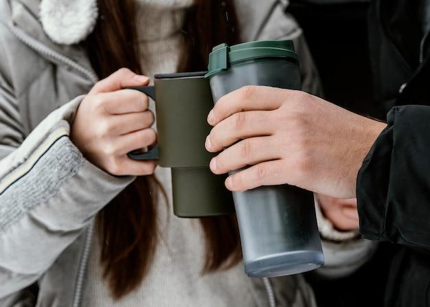 Koppel met een warm drankje in de kofferbak van de auto tijdens een roadtrip