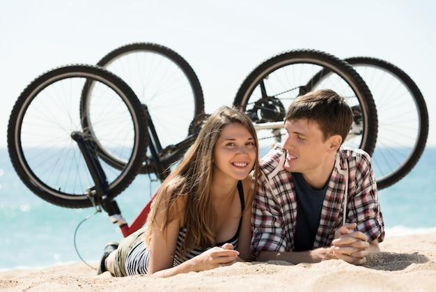 Koppel met fietsen op het strand