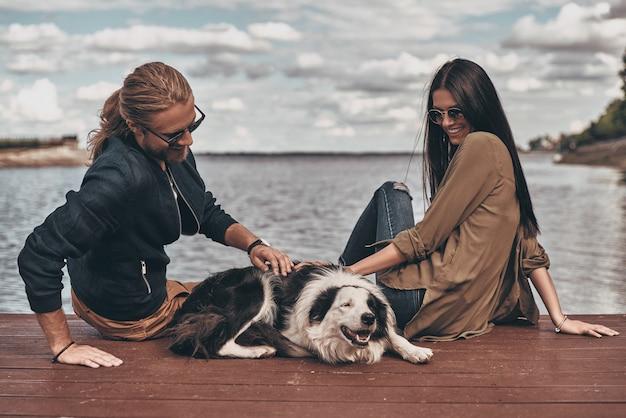 Koppel met hond. mooie jonge paar spelen met hond zittend in de buurt van het meer buiten