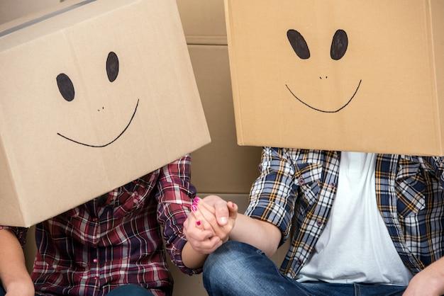 Koppel met kartonnen dozen op hun hoofd met smileygezicht.