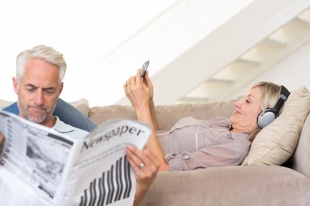 Koppel met krant en mobiel in de woonkamer