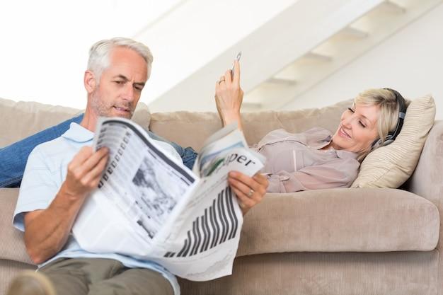 Koppel met krant en mobiel in woonkamer thuis