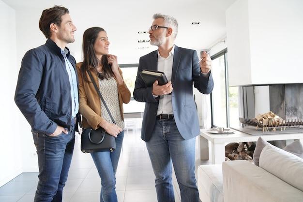 Koppel met makelaar in onroerend goed een bezoek aan modern huis