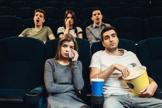 Koppel met popcorn in de bioscoop. saai filmconcept, mensen kijken naar film