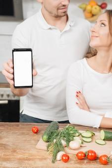 Koppel met smartphonesjabloon in keuken