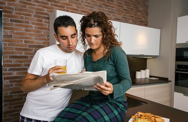 Koppel ontbijten in de keuken en lezen de krant
