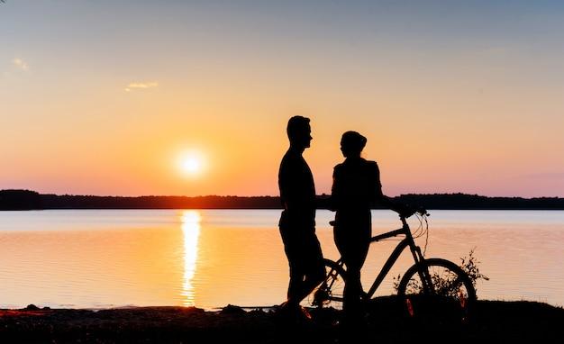 Koppel op een fiets bij zonsondergang aan het meer Premium Foto