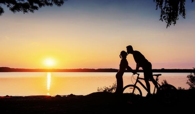 Koppel op een fiets bij zonsondergang aan het meer