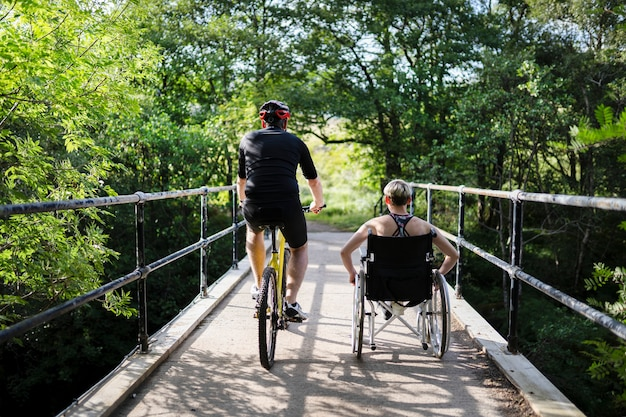 Koppel op een oefening samen op een fiets en in een rolstoel