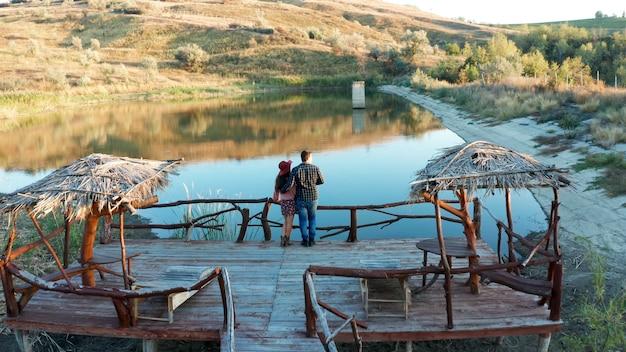 Koppel op een pontonbrug in een vakantie in landelijk gebied met een meer, drone luchtbeelden