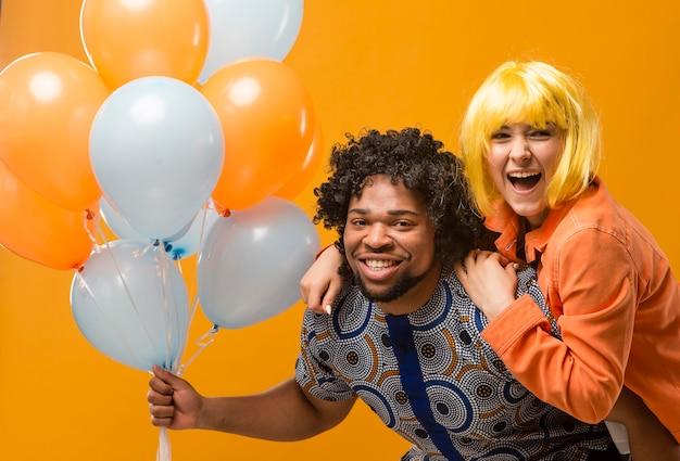 Koppel op feestje met plezier en ballonnen vast te houden Premium Foto
