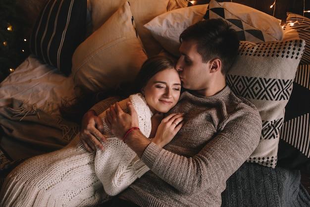 Koppel op het bed in de slaapkamer. donker interieur. nieuwjaar en kerstmis. knuffels en kussen. liefde. witte trui en hoge sokken. romantische ontmoeting. liefhebbers van een date. rode draad om de pols.