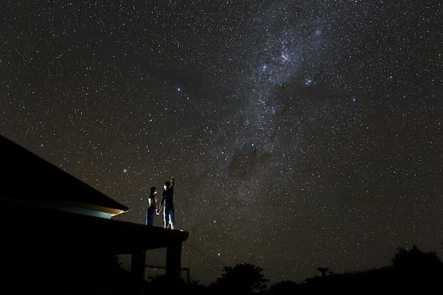 Koppel op het dak kijken mliky manier en sterren aan de nachtelijke hemel