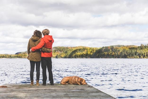 Koppel op het dok met een hond, kijkend naar weergave