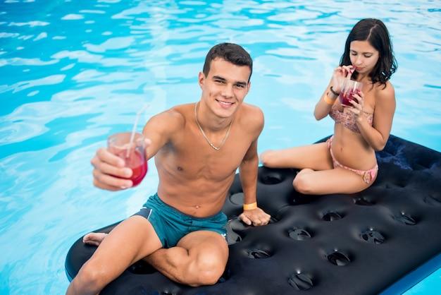 Koppel op opblaasbare matras in zwembad