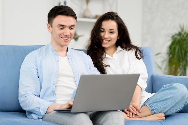 Koppel op sofa thuis met laptop