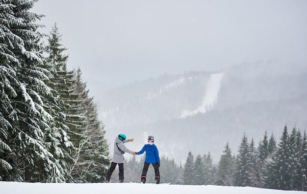Koppel snowboarders die op de helling staan