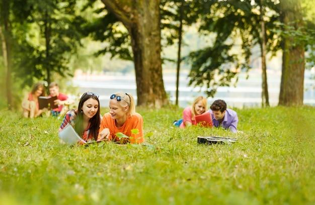 Koppel succesvolle studenten aan een leerboek in een park op een zonnige dag