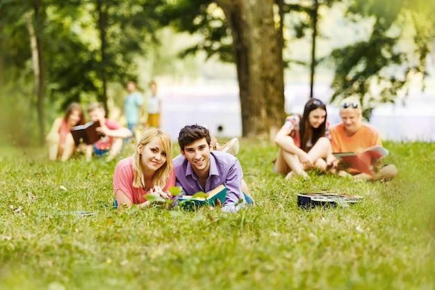 Koppel succesvolle studenten met een leerboek in een park op een zonnige dag