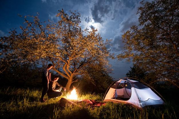 Koppel toeristen bij kampvuur in de buurt van tent