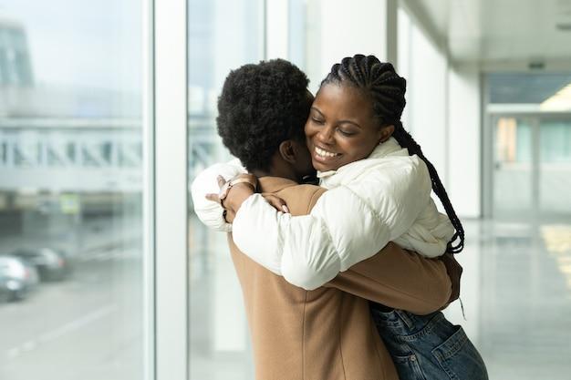 Koppelreünie op luchthaven afrikaanse vrouw ontmoette knuffelvriend die arriveerde na vakantie of reis naar het buitenland