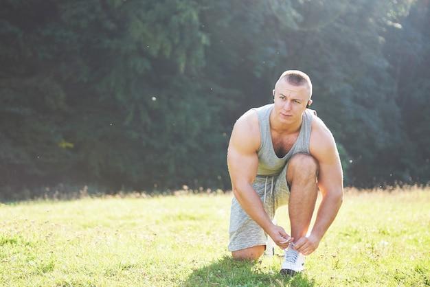 Koppelverkoop sportschoen. een jonge sportman die zich klaarmaakt voor atletiek- en fitnesstraining buitenshuis.