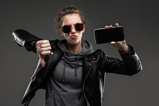 Koppig kaukasisch meisje met ruwe gelaatstrekken in een zwarte jas toont haar telefoon en houdt niet van geïsoleerd op zwarte muur