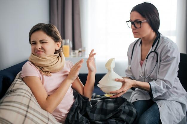 Koppig ziek meisje krimpt en houdt de ogen gesloten. ze wil geen inhalatieprocedure doen. vrouwelijke arts houdt witte inhalator en geeft het aan kind. ze zitten in één kamer.