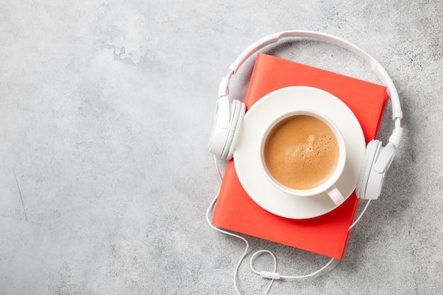 Koptelefoon, boek en kopje koffie op betonnen ondergrond