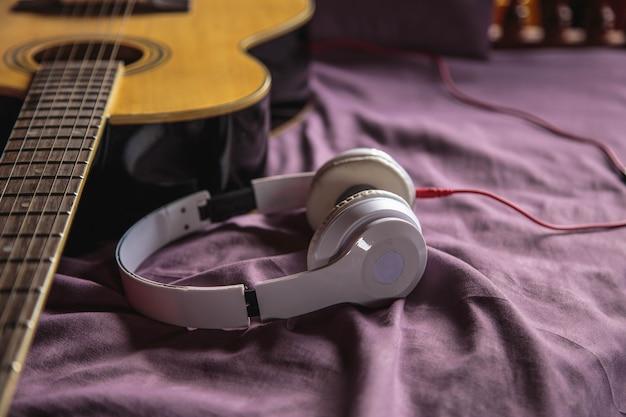 Koptelefoon en klassieke gitaar in bed