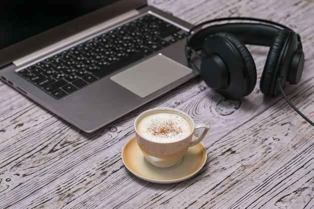 Koptelefoon, laptop en een kopje koffie op een houten tafel