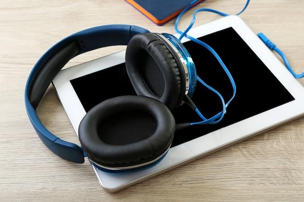 Koptelefoon met tablet op houten tafel close-up