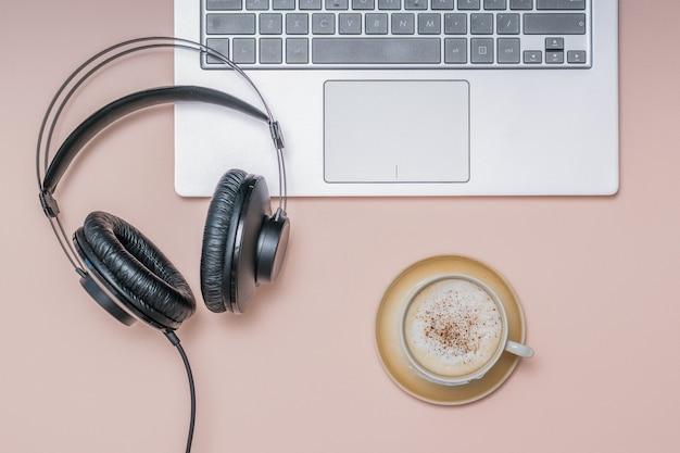 Koptelefoon op de laptop en een kopje koffie met kaneel op een lichte ondergrond