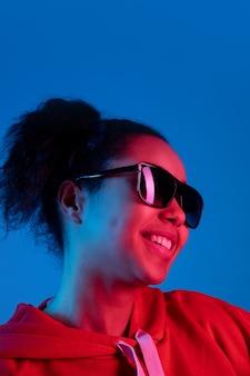 Koptelefoon. portret van de afro-amerikaanse vrouw geïsoleerd op blauwe studio achtergrond in veelkleurige neonlicht. mooi vrouwelijk model. concept van menselijke emoties, gezichtsuitdrukking, verkoop, advertentie, mode.