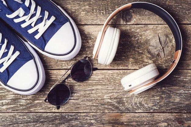 Koptelefoons en sneakers op rustieke achtergrond. set trendy herenaccessoires, bovenaanzicht. modieuze sneakers, zonnebrillen en moderne draadloze koptelefoons. mannenmode. kopieer ruimte. hipster stedelijke stijl