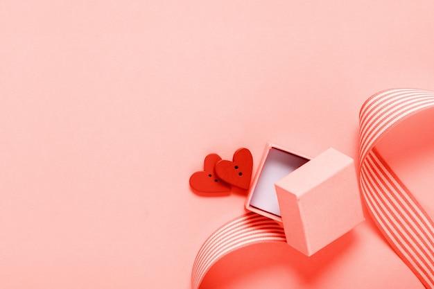 Koraal geschenkdoos en twee harten op koraal achtergrond, valentijnsdag