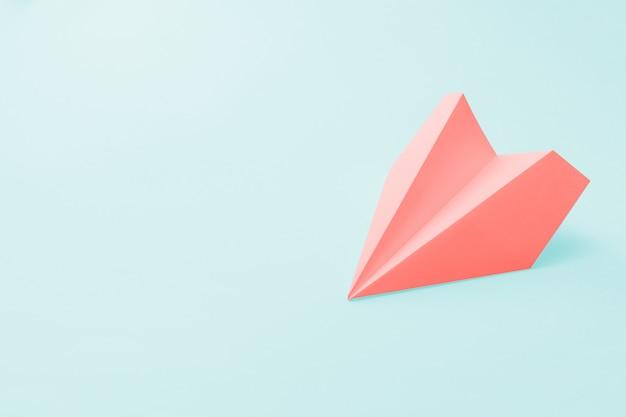 Koraal papieren vliegtuig op lichtblauw
