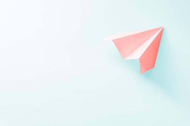 Koraal papieren vliegtuigje op een lichtblauwe achtergrond. trendy 2019 kleurenconcept