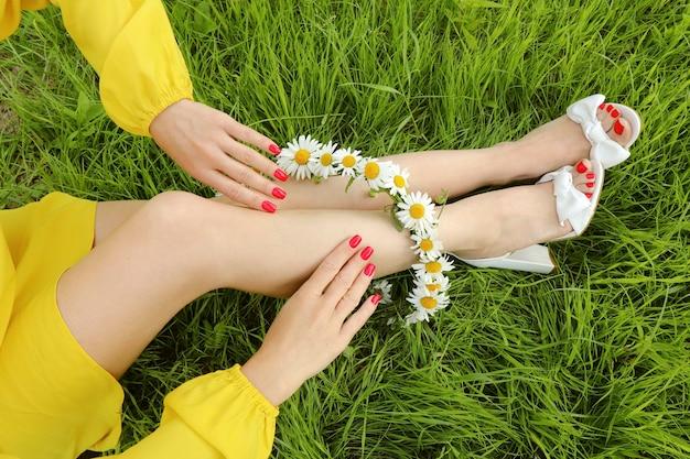 Koraal toplaag op de nagels met een boeket madeliefjes op het meisje dat in de zomer op het gras zit.