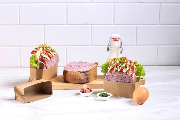Koreaans broodje paars brood (egg drop) met ei, sla, mayonaise, kaas, peterselie, saus. geserveerd met melk. witte achtergrondconcept voor bakkerij of advertentie