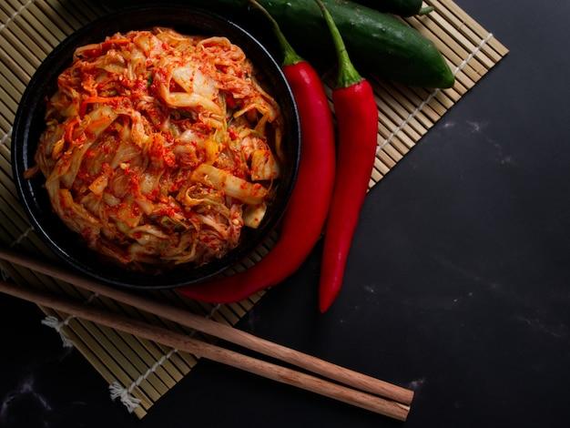 Koreaans eten, kool kimchi in zwarte schotel ingesteld op donkere achtergrond.