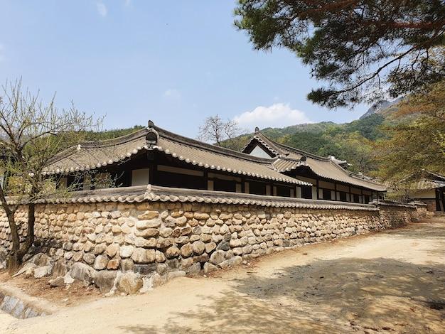 Koreaans gebouw omgeven door bergen onder een blauwe lucht
